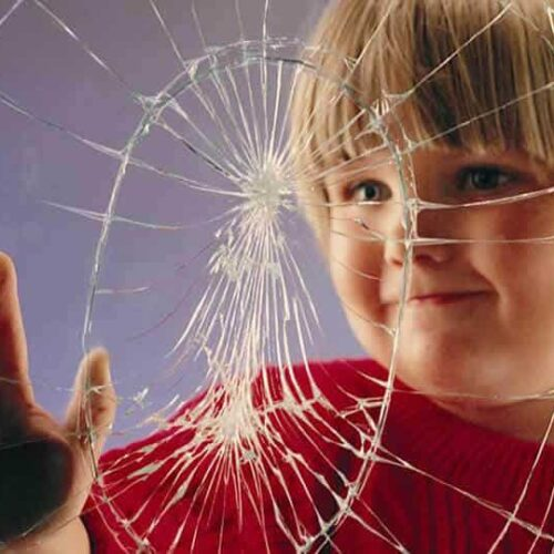 child putting his hand to glass with safety window film installed
