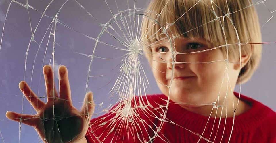 Child touching glass covered with safety shatterproof window film