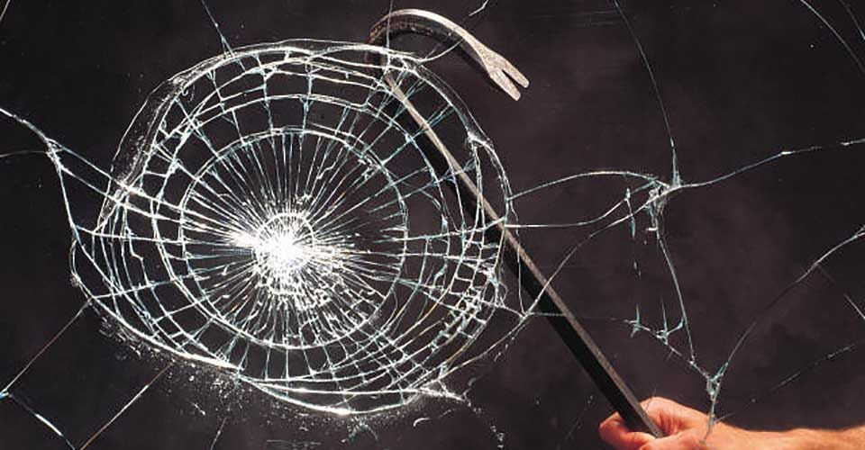 Crowbar hitting a window protected by security shatterproof film