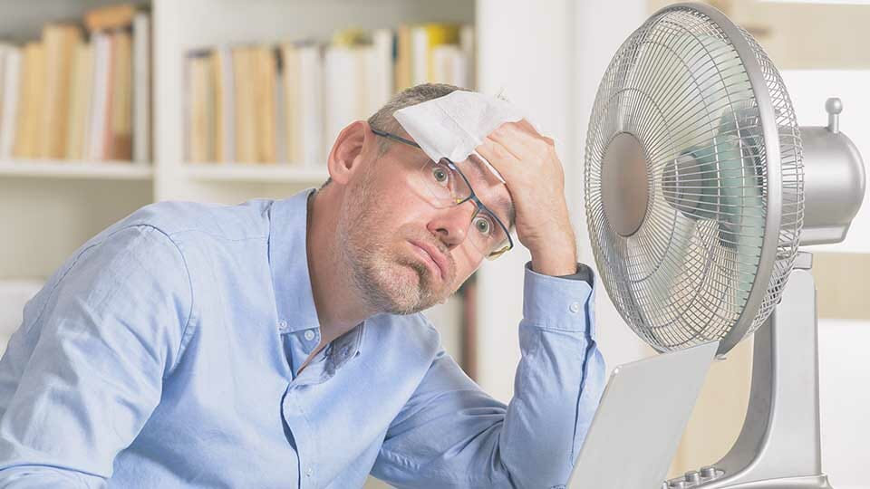 Man with a fan to try and cool down due to not having solar window film installed