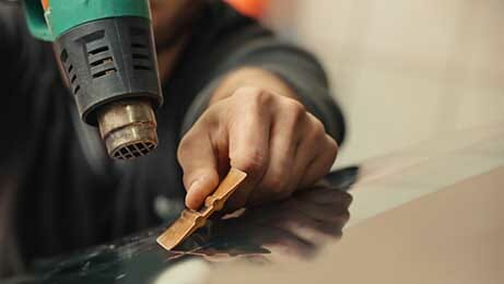 man with heat gun and squeegee window tinting tools