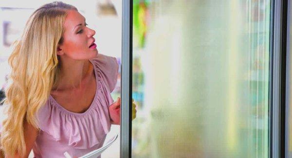 woman looking at at fogging freezer door that needs anti condensation window film