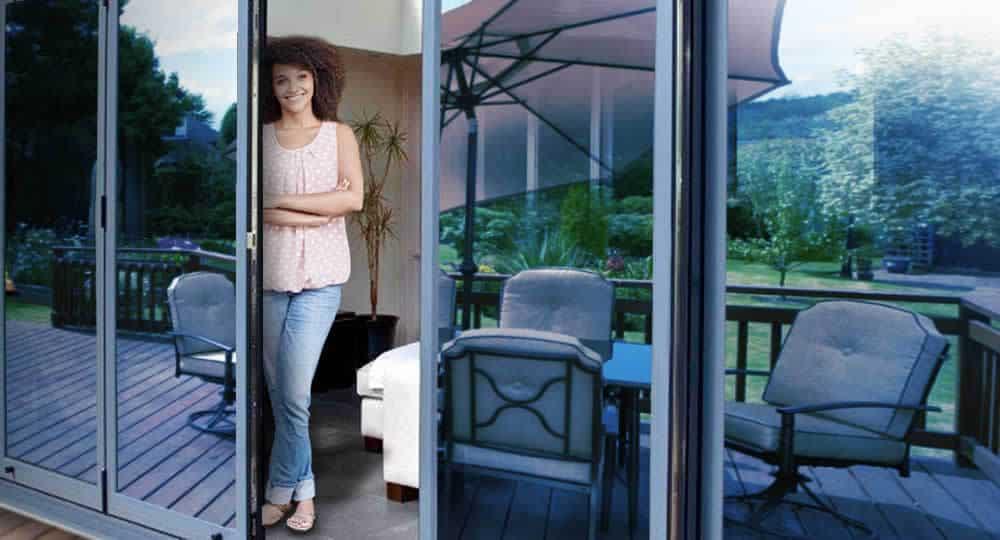 woman standing in open patio door with blue reflective window film installed