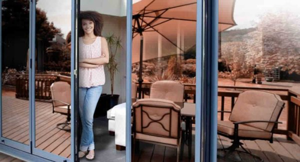 woman standing in open patio door with bronze reflective window film installed