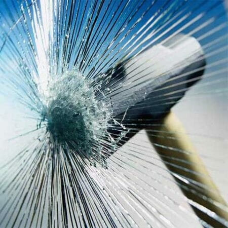 Hammer impact on glass with security window film protecting it