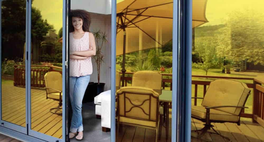 woman standing in open patio door with gold reflective window film installed