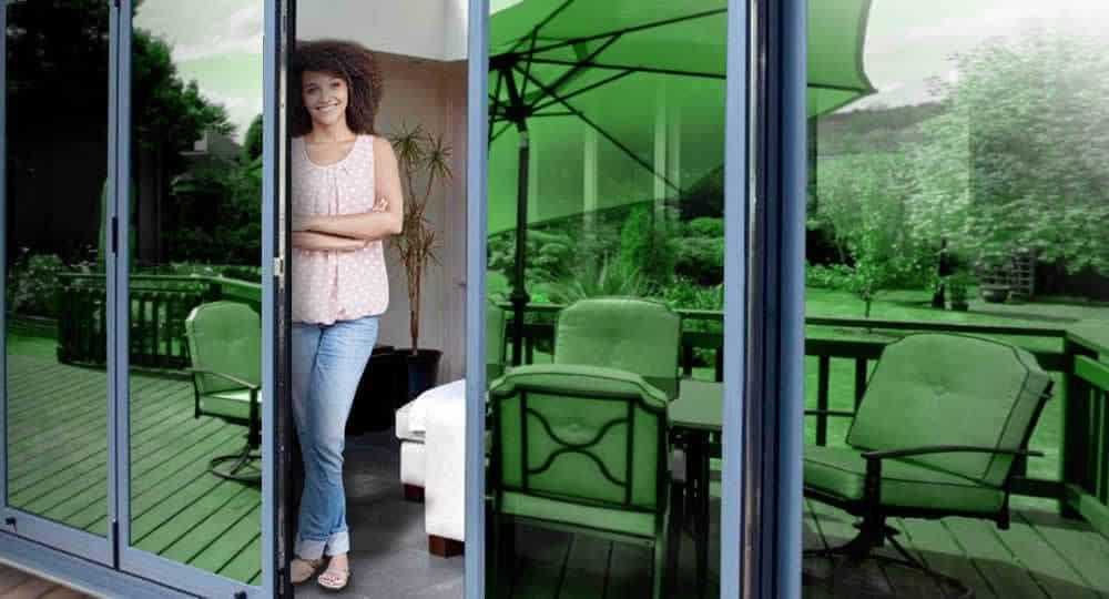 woman standing in open patio door with green reflective window film installed