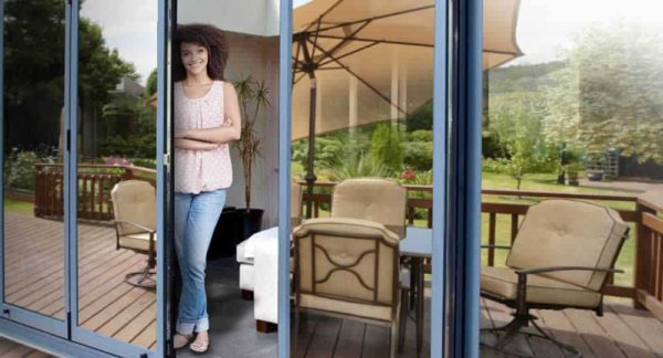 woman standing in open patio door with silver reflective window film installed