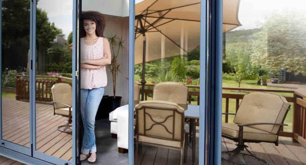 woman standing in open patio door with silver reflective window film installed